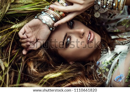 Beautiful hippie girl lying in a grass. Modern boho style. Beauty, fashion,  #1110661820