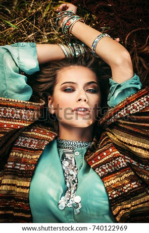 Beautiful hippie girl lying in a grass. Modern boho style. Beauty, fashion,  #740122969