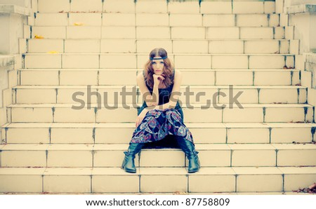 Beautiful hippie girl sitting on a vintage stairs in autumn scenery wearing maxi long dress and gorgeous make up.