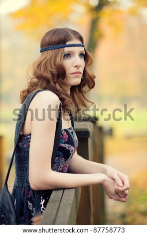 Beautiful hippie girl thinking on a wooden bridge in autumn scenery wearing maxi long dress and gorgeous make up.