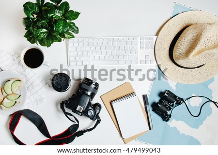 Beautiful hipster flatlay with hat, dslr camera, lens, coffee, map, flower, notebook and binocular. Working space surface top view. Creative work table for photographer, traveller, blogger
