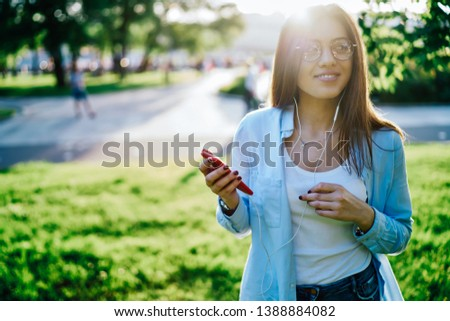 Beautiful hipster girl dressed in casual wear walking outdoors in green park and listening audio music in modern earphones from music playlist downloaded on smartphone device via public 4G internet