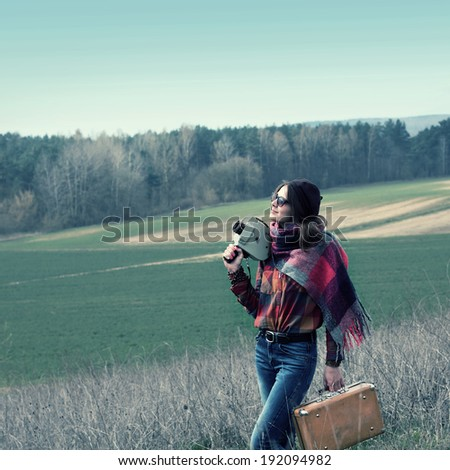Beautiful hipster girl in a beret makes movies on vintage movie camera. modern girl travels to wildlife with vintage camera