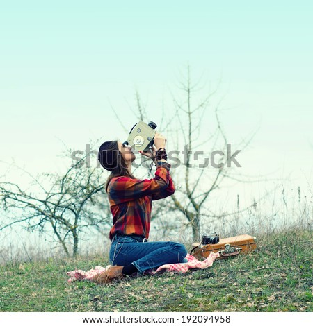 Beautiful hipster girl in a beret makes movies on vintage movie camera. pictures of the sky sitting on rug