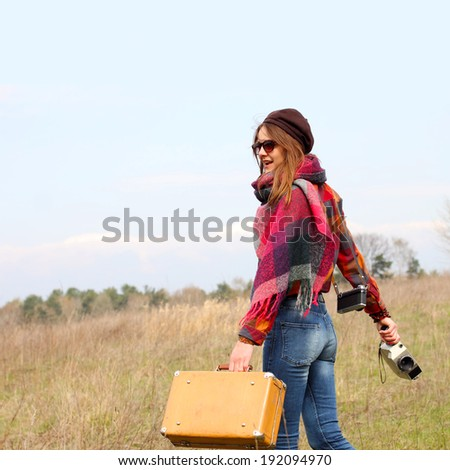 Beautiful hipster girl in a beret with vintage suitcase and vintage movie camera. modern girl travels to wildlife with vintage camera. view from the back