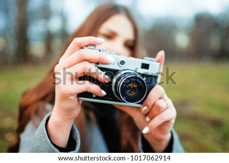 Beautiful hipster girl shooting with retro camera