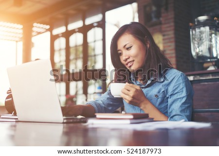Beautiful hipster woman using laptop at cafe while drinking coffee, Relaxing holiday concept. #524187973