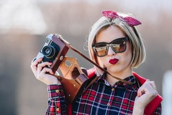 Beautiful hipster woman with braces using unknown vintage analog camera. Wearing red toned clothes with neutral color background. photographer