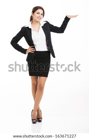 Beautiful hispanic business woman smiling over a white background and showing something