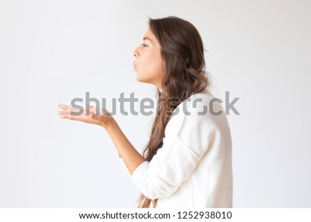 Beautiful Hispanic girl blowing air kiss from hands. Profile portrait of stylish young woman. Isolated on white. Love concept Foto stock ©