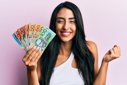 Beautiful hispanic woman holding australian dollars screaming proud, celebrating victory and success very excited with raised arm