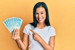 Beautiful hispanic woman holding 100 brazilian real banknotes smiling happy pointing with hand and finger