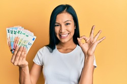 Beautiful hispanic woman holding euro banknotes doing ok sign with fingers, smiling friendly gesturing excellent symbol