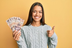 Beautiful hispanic woman holding 500 mexican pesos banknotes smiling happy and positive, thumb up doing excellent and approval sign