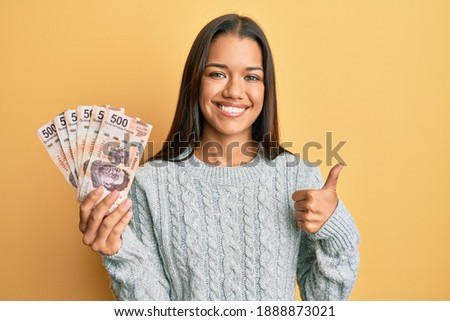 Beautiful hispanic woman holding 500 mexican pesos banknotes smiling happy and positive, thumb up doing excellent and approval sign  Foto stock ©