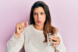 Beautiful hispanic woman holding pill and glass of water depressed and worry for distress, crying angry and afraid. sad expression.