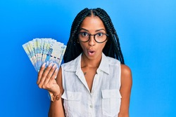 Beautiful hispanic woman holding south african 100 rand banknotes scared and amazed with open mouth for surprise, disbelief face