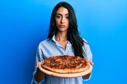 Beautiful hispanic woman holding tasty pepperoni pizza skeptic and nervous, frowning upset because of problem. negative person.