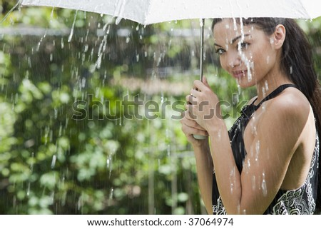Beautiful Hispanic woman holding umbrella out in the rain