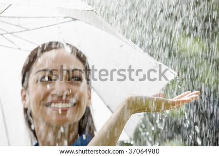 Beautiful Hispanic woman holding umbrella out in the rain