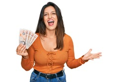 Beautiful hispanic woman holding 10 united kingdom pounds banknotes celebrating victory with happy smile and winner expression with raised hands