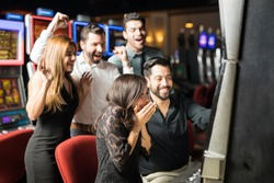 Beautiful Hispanic woman looking excited about hitting the jackpot in a slot machine while her friends celebrate with her