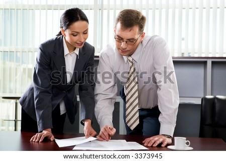 Beautiful Hispanic woman showing a document to her colleague