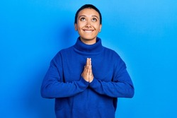 Beautiful hispanic woman with short hair wearing turtleneck sweater begging and praying with hands together with hope expression on face very emotional and worried. begging.