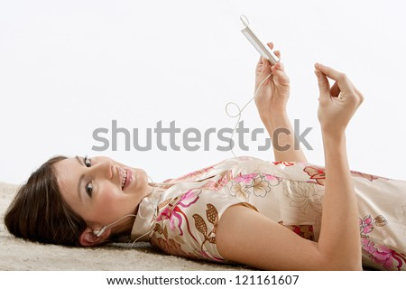 Beautiful hispanic young woman laying down on a furry carpet at home, listening to music with her earphones and clicking her fingers following the rhythm, relaxing.