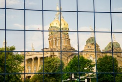 Beautiful historical  Des Moines Iowa State Capitol reflected in glass office building windows.