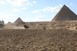 Beautiful historical street view on a cloudy day. Scene with riding tourist near pyramid in Egyptian desert. People travel to the African continent for look of a UNESCO World Heritage Site.