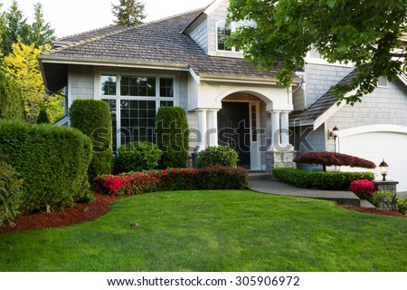 Beautiful home exterior during late spring season with green lawn.