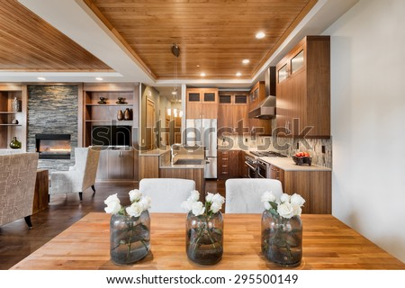 Beautiful home interior with open floor plan: includes dining room, kitchen, and living room with dining room table, flowers, wood strip tray ceiling, cabinets, hardwood floors, and fireplace