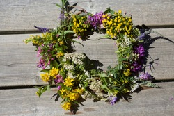 Beautiful home-made mid summer wreath of wildflowers in white yellow and pink and blue.Tradition in Nordic countries for summer celebration