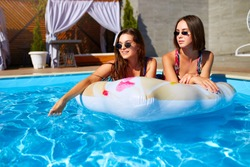 Beautiful hot pretty girls in bikini are swimming in a pool on an inflatable donut floaty. Attractive slim women in swimsuits and sunglasses have fun relaxing and sunbathing on sunny day summer party.