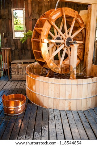Beautiful hot tub in the garden with a watermill inside of it.