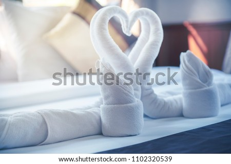 Beautiful hotel for honeymoon sweet.Swan couple put on honeymoon bed look like heart shape .Bed ,clean pillows and bed sheets in bedroom.Many hotel resort or home make relax area and comfort zone