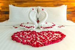 Beautiful hotel for honeymoon sweet.Swan couple put on honeymoon bed look like heart shape with rose petals for honeymoon lover.The staff hotel put yellow lighting in the room make romantic feeling.