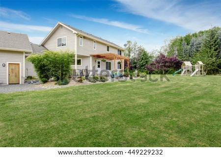 Beautiful house backyard with well kept lawn, patio area and playground at the background #449229232