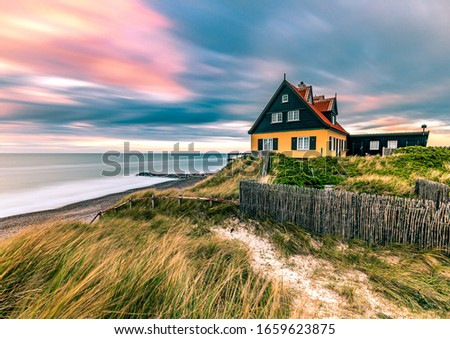 Beautiful House in typical yellow color on the beach with sea view during colorful sunset. Skagen coastline in North Jutland in Denmark, Skagerrak, North Sea Foto stock ©