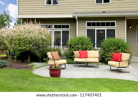 Beautiful house with backyard sitting area with sofas and chairs.