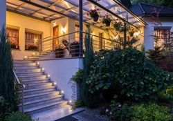 Beautiful house with garden in the evening with lamps on
