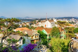 Beautiful houses with tile roofs in the Da Lat city (Dalat) on the blue sky background in Vietnam. Da Lat and the surrounding area is a popular tourist destination of Asia.