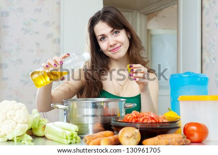 beautiful housewife cook vegetables with oil at her kitchen at home