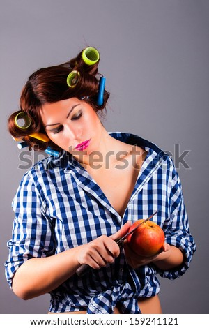 beautiful housewife with curlers holding apple and the knife