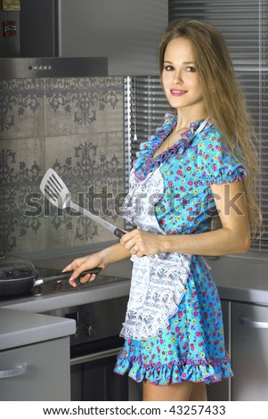 beautiful housewife with serving spoon in the kitchen