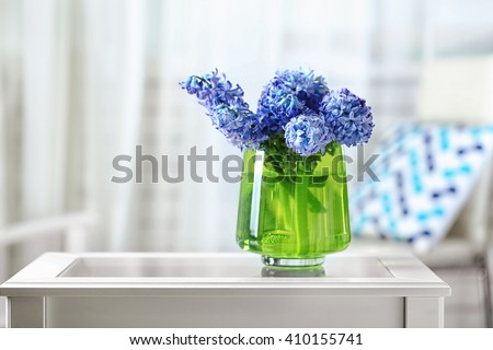 Stock Photo Beautiful hyacinth flowers in glass vase on light blurred background