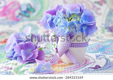 beautiful hydrangea flowers in a pot decorated with a heart on a beautiful tablecloth.