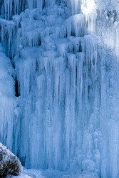 Beautiful ice structures of a frozen waterfall, pretty icicles forming an interesting pattern on a dark rock, creating a cold eerie and moody atmosphere in an ice cave in the mountains