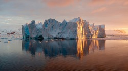 Beautiful iceberg reflecting in the water. Photo taken at sunset in Antarctica.